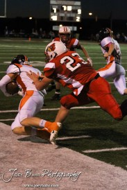 Hoisington Cardinal Avery Urban (#23) pushes Larned Indian Gage Stude (#2) out of bounds during the Larned at Hoisington High School Football game with Hoisington winning 27 to 9 at Elton Brown Field in Hoisington, Kansas on October 11, 2013. (Photo: Joey Bahr, www.joeybahr.com)