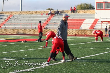 Hoisington Cardinal Assistant Coach Zach Baird pats a player during warmups for the KSHSAA Class 4A District 15 Football game between Scott City and Hoisington with Scott City winning 14 to 0 at Elton Brown Field in Hoisington, Kansas on October 18, 2013. (Photo: Joey Bahr, www.joeybahr.com)