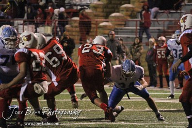 Hoisington Cardinal Avery Urban (#23) finds a hole to run through during the KSHSAA Class 4A District 15 Football game between Scott City and Hoisington with Scott City winning 14 to 0 at Elton Brown Field in Hoisington, Kansas on October 18, 2013. (Photo: Joey Bahr, www.joeybahr.com)