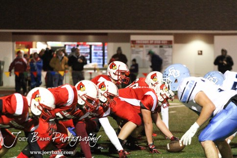 Hoisington Cardinal Taylor Richter (#7) calls for the ball to be hiked during the KSHSAA Class 4A District 15 Football game between Scott City and Hoisington with Scott City winning 14 to 0 at Elton Brown Field in Hoisington, Kansas on October 18, 2013. (Photo: Joey Bahr, www.joeybahr.com)