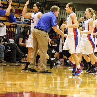 Ellinwood Lady Eagle Head Coach Kyle Kriegh congratulate his players on taking an early lead during the 2014 Hoisington Cardinal Winter Jam Girls Championship basketball game with the Ellinwood Lady Eagles versus the Minneapolis Lady Lions with Ellinwood winning 57 to 48 at the Hoisington Activity Center in Hoisington, Kansas on January 25, 2014. (Photo: Joey Bahr, www.joeybahr.com)