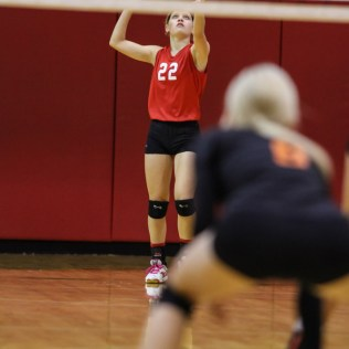 Kingman Lady Eagle Sydney Bangert (#22) serves the ball during the Kingman Lady Eagles versus Larned Lady Indians volleyball match with Kingman winning 25-21, 24-26, 25-15 at Hoisington Activity Center in Hoisington, Kansas on September 9, 2014. (Photo: Joey Bahr, www.joeybahr.com)