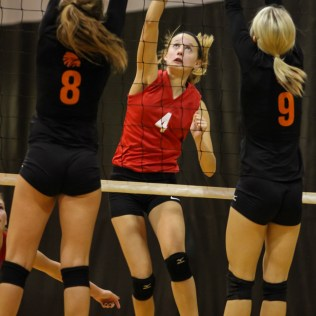 Kingman Lady Eagle Shyann Jackson (#4) tries to hit the ball between the wall of Larned Lady Indians Jessica Gobin (#8) and Kaitlyn Nolde (#9) during the Kingman Lady Eagles versus Larned Lady Indians volleyball match with Kingman winning 25-21, 24-26, 25-15 at Hoisington Activity Center in Hoisington, Kansas on September 9, 2014. (Photo: Joey Bahr, www.joeybahr.com)