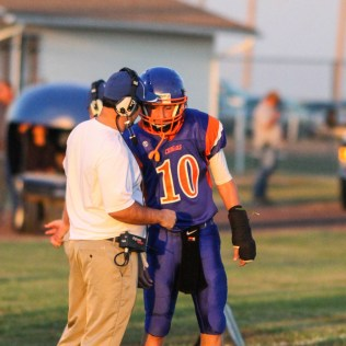 Otis-Bison Cougar Assistant Coach Curtis Little gives the next play to Kade Urban (#10) during the Otis-Bison versus Kinsley High School 8-Man Football Game with Otis-Bison winning 104 to 70 which set a new state record for combined points in a game at Cougar Field at Otis-Bison High School in Otis, Kansas on September 26, 2014. (Photo: Joey Bahr, www.joeybahr.com)
