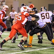 Hoisington Cardinal Ben Schneider (#65) locks up with Smoky Valley Viking Clayton Couchman (#56) during the Hoisington High School versus Smoky Valley football game with Hoisington winning 33 to 12 at Eldon Brown Field in Hoisington, Kansas on October 10, 2014. (Photo: Joey Bahr, www.joeybahr.com)