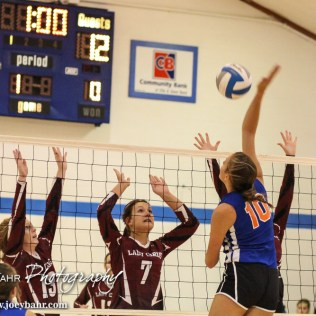 Otis-Bison Lady Cougar Taylor Regan (#10) goes for a kill as Plainville Lady Cardinal Lyric Dewey (#7) goes up for a block during the Otis-Bison/LaCrosse Volleyball Tournament Pool Play at Otis-Bison High School in Otis, Kansas on September 13, 2014. (Photo: Joey Bahr, www.joeybahr.com)