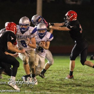 Spearville Lancer Luke Heskamp (#4) rushes with the ball as Nathan Stein (#8) lead blocks Hodgeman County Longhorn Kolt Washburn (#8) during the Spearville at Hodgeman County High School Football Game with Spearville winning 50 to 28 at Sayler Field in Jetmore, Kansas on October 24, 2014. (Photo: Joey Bahr, www.joeybahr.com)
