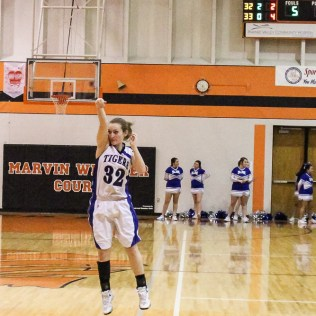 St. John Lady Tiger Brandi Hanson (#32) shoots a three point shot during the Seventh Annual Keady Basketball Classic First Round game between the St. John Lady Tigers and the Kiowa County Lady Mavericks with St. John winning 47 to 31 at Larned Middle School in Larned, Kansas on December 9, 2014. (Photo: Joey Bahr, www.joeybahr.com)