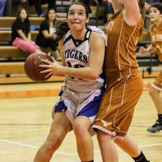 St. John Lady Tiger Teresa Christie (#33) goes for a layup during the Seventh Annual Keady Basketball Classic First Round game between the St. John Lady Tigers and the Kiowa County Lady Mavericks with St. John winning 47 to 31 at Larned Middle School in Larned, Kansas on December 9, 2014. (Photo: Joey Bahr, www.joeybahr.com)