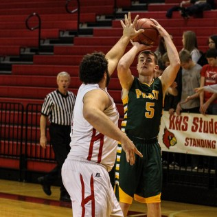 Hoisington Cardinal Seth Owen (#4) tries to block a shot from Pratt Greenback Derek Barnard (#5) during the Pratt Greenbacks at Hoisington Cardinals Boys Basketball game with Pratt winning 66 to 34 at Hoisington Activity Center in Hoisington, Kansas on January 6, 2015. (Photo: Joey Bahr, www.joeybahr.com)