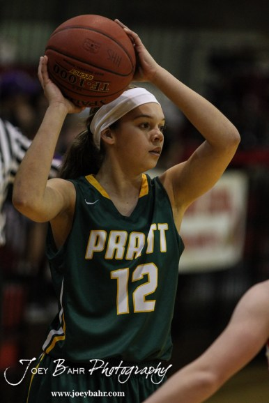 Pratt Lady Greenback Kelsey Smith-Potter (#12) looks for a teammate to pass the ball to during the Pratt Lady Greenbacks at Hoisington Lady Cardinals Girls Basketball game with Pratt winning 34 to 23 at Hoisington Activity Center in Hoisington, Kansas on January 6, 2015. (Photo: Joey Bahr, www.joeybahr.com)