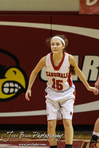 Hoisington Lady Cardinal Emma Harmon (#15) watches a play develop while on defense during the Pratt Lady Greenbacks at Hoisington Lady Cardinals Girls Basketball game with Pratt winning 34 to 23 at Hoisington Activity Center in Hoisington, Kansas on January 6, 2015. (Photo: Joey Bahr, www.joeybahr.com)