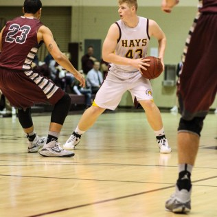 Hays Indian Shane Berens (#43) looks for a teammate to pass to during the 4A Division I Sub-State First Round Game with the Hays Indians and Buhler Crusaders with Hays winning 60 to 53 at Hays High School in Hays, Kansas on March 5, 2015. (Photo: Joey Bahr, www.joeybahr.com)