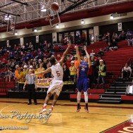 Hoisington Cardinal Cameron Davis (#5) tries to block a three point shot by Ellinwood Eagle Nathan Monday (#35) during the 2016 Hoisington Winter Jam Boys Semi-Final Basketball game between the Hoisington Cardinals and the Ellinwood Eagles with Hoisington winning 42 to 39 of Hoisington Activity Center in Hoisington, Kansas on January 22, 2016. (Photo: Joey Bahr, www.joeybahr.com)