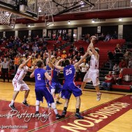 Hoisington Cardinal Tyler Specht (#11) passes the ball as four Ellinwood Eagles crash in on him during the 2016 Hoisington Winter Jam Boys Semi-Final Basketball game between the Hoisington Cardinals and the Ellinwood Eagles with Hoisington winning 42 to 39 of Hoisington Activity Center in Hoisington, Kansas on January 22, 2016. (Photo: Joey Bahr, www.joeybahr.com)