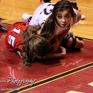 LaCrosse Lady Leopard Mary Lacy (#12) looks up to see the call as her and Hoisington Lady Cardinal Emma Harmon (#15) battle for the ball during the 2016 Hoisington Winter Jam Girls Semi-Final Basketball game between the LaCrosse Lady Leopards and the Hoisington Lady Cardinals with LaCrosse winning 42 to 39 of Hoisington Activity Center in Hoisington, Kansas on January 22, 2016. (Photo: Joey Bahr, www.joeybahr.com)