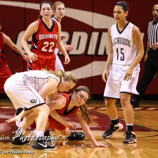 Hoisington Lady Cardinal Karisa Schremmer (#4) reaches for the ball as LaCrosse Lady Leopard Mary Lacy (#12) tries to maintain control during the 2016 Hoisington Winter Jam Girls Semi-Final Basketball game between the LaCrosse Lady Leopards and the Hoisington Lady Cardinals with LaCrosse winning 42 to 39 of Hoisington Activity Center in Hoisington, Kansas on January 22, 2016. (Photo: Joey Bahr, www.joeybahr.com)