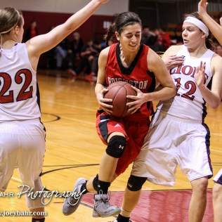 Hoisington Lady Cardinal Rylie Koester (#12) drives into the lane as Minneapolis Lady Lion Jaidra Lott (#12) looks to get out of the way during the 2016 Hoisington Winter Jam Girls Thrid Place Basketball game between the Hoisington Lady Cardinals and the Minneapolis Lady Lions with Hoisington winning 48 to 43 of Hoisington Activity Center in Hoisington, Kansas on January 23, 2016. (Photo: Joey Bahr, www.joeybahr.com)