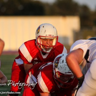 Hoisington Cardinal Tyler Specht (#1) calls for the ball to be hiked during the Hoisington Cardinal versus Larned Indian Football game with Hoisington winning 53 to 21 at Elton Brown Field in Hoisington, Kansas on September 4, 2015. (Photo: Joey Bahr, www.joeybahr.com)