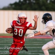 Hoisington Cardinal Jonathan Ball (#30) prepares to stiff arm Larned Indian Isiah Perez (#84) during the Hoisington Cardinal versus Larned Indian Football game with Hoisington winning 53 to 21 at Elton Brown Field in Hoisington, Kansas on September 4, 2015. (Photo: Joey Bahr, www.joeybahr.com)