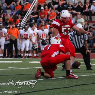Hoisington Cardinal Christopher Wright (#53) kicks a Point After Touchdown during the Hoisington Cardinal versus Larned Indian Football game with Hoisington winning 53 to 21 at Elton Brown Field in Hoisington, Kansas on September 4, 2015. (Photo: Joey Bahr, www.joeybahr.com)