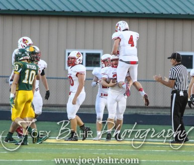 Hoisington Cardinal Kyle Lang (#4) congratulates Hoisington Cardinal Sean Urban (#23) on scoring a touchdown. The Hoisington Cardinals defeated the Pratt Greenbacks 32 to 14 at Zerger Field in Pratt, Kansas on September 30, 2016. (Photo: Joey Bahr, www.joeybahr.com)
