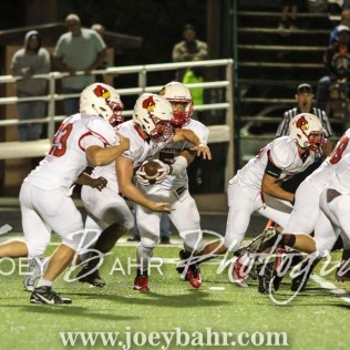 Hoisington Cardinal Tyler Specht (#1) hands the ball off to Hunter Hanzlick (#27). The Hoisington Cardinals defeated the Pratt Greenbacks 32 to 14 at Zerger Field in Pratt, Kansas on September 30, 2016. (Photo: Joey Bahr, www.joeybahr.com)