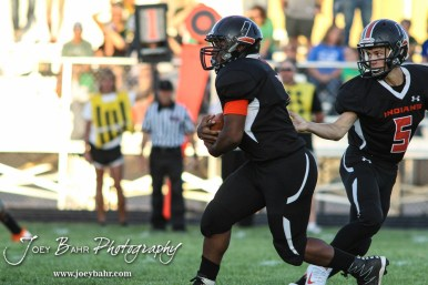 Pratt Greenback Travis Theis (#5) hands the ball off to Anthony McConnell (#1). The Pratt Greenbacks win 31 to 16 over the Larned Indians at Earl Roberts Field in Larned, Kansas on September 2, 2016. (Photo: Joey Bahr, www.joeybahr.com)