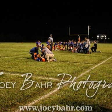 The Otis-Bison Cougars take a knee as trainers and coaches tend to Justin Scott (#9). The Otis-Bison Cougars defeated the Greeley County Jackrabbits 62 to 6 at Cougar Field in Otis, Kansas on October 7, 2016. (Photo: Joey Bahr, www.joeybahr.com)