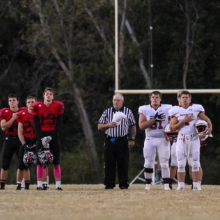 Team Captains and Referees stand at attention for the National Anthem. The Hoisington Cardinals defeated the Ellsworth Bearcats 39 to 20 at Shanelac Field in Ellsworth, Kansas on October 14, 2016. (Photo: Joey Bahr, www.joeybahr.com)