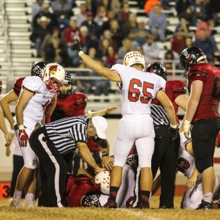Hoisington Cardinal Ben Schneider (#65) signals that his team recovered the ball, the Refs pulled that the ball remain with Ellsworth. The Hoisington Cardinals defeated the Ellsworth Bearcats 39 to 20 at Shanelac Field in Ellsworth, Kansas on October 14, 2016. (Photo: Joey Bahr, www.joeybahr.com)