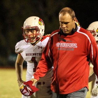 Hoisington Cardinal Head Coach Zach Baird and Tyler Specht (#1) discuss an important matter as they walk to the position of the ball for the start of the Fourth Quarter. The Hoisington Cardinals defeated the Ellsworth Bearcats 39 to 20 at Shanelac Field in Ellsworth, Kansas on October 14, 2016. (Photo: Joey Bahr, www.joeybahr.com)