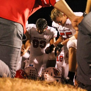 The Hoisington Cardinals kneel in prayer following the game. The Hoisington Cardinals defeated the Ellsworth Bearcats 39 to 20 at Shanelac Field in Ellsworth, Kansas on October 14, 2016. (Photo: Joey Bahr, www.joeybahr.com)