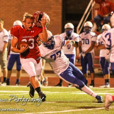 Hoisington Cardinal Sean Urban (#23) tries to hold on to his helmet as he carries the ball. The Hoisington Cardinals defeated the Lyons Lions to win the KSHSAA Class 3A District 15 Championship at Elton Brown Field in Hoisington, Kansas on October 27, 2016. (Photo: Joey Bahr, www.joeybahr.com)