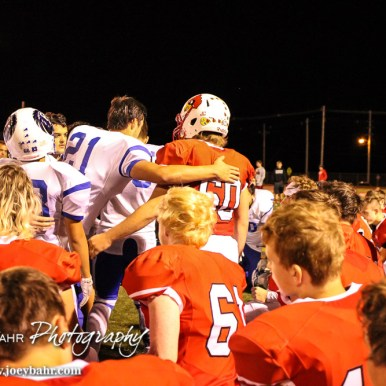 Lyons Lions console Hoisington Cardinal Jeremy Breit (#60) on the loss of his father this week. The Hoisington Cardinals defeated the Lyons Lions to win the KSHSAA Class 3A District 15 Championship at Elton Brown Field in Hoisington, Kansas on October 27, 2016. (Photo: Joey Bahr, www.joeybahr.com)