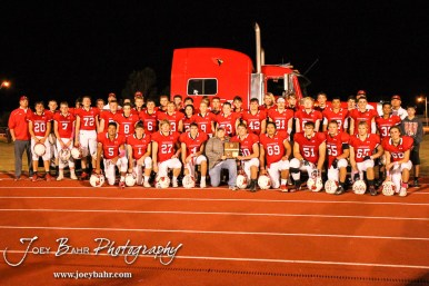 The Hoisington Cardinals take a picture with the District 15 Champion Trophy infant of John Briet's semi-truck. The Hoisington Cardinals defeated the Lyons Lions to win the KSHSAA Class 3A District 15 Championship at Elton Brown Field in Hoisington, Kansas on October 27, 2016. (Photo: Joey Bahr, www.joeybahr.com)