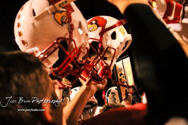 The Hoisington Cardinals hold up their helmets and the Bi-District Champions Trophy. The Hoisington Cardinals defeated the Lakin Broncs in the KSHSAA Class 3A Bi-District game with a score of 56 to 13 at Elton Brown Field in Hoisington, Kansas on November 1, 2016. (Photo: Joey Bahr, www.joeybahr.com)