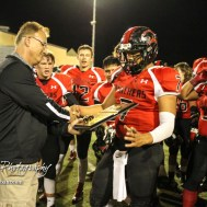 Great Bend Athletic Director David Meter presents the Class 5A Regional Champion Trophy to Great Bend Panther Jacob Murray (#7). The Great Bend Panthers defeated the Andover Trojans in the KSHSAA Class 5A Regional playoff game with a score of 16 to 7 at Memorial Stadium in Great Bend, Kansas on November 4, 2016. (Photo: Joey Bahr, www.joeybahr.com)
