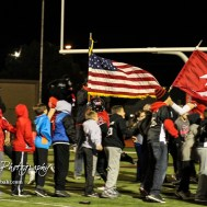 Great Bend Panther Dominique Rideaux (#14) leads his teammates onto the field while carrying the flag. The Great Bend Panthers defeated the Valley Center Hornets to win the KSHSAA Class 5A Sectional by a score of 28 to 24 at Memorial Field in Great Bend, Kansas on November 11, 2016. (Photo: Joey Bahr, www.joeybahr.com)