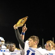 Goddard Lion Blake Sullivan (#11) holds the Sub-State Champion Trophy aloft after the game. The Goddard Lions defeated the Great Bend Panthers to win the KSHSAA Class 5A Sub-State Championship by a score of 50 to 21 at Memorial Field in Great Bend, Kansas on November 18, 2016. (Photo: Joey Bahr, www.joeybahr.com)