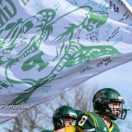 A flag signed by the teammates flies over the Pratt Greenbacks as they take the field. The Pratt Greenbacks defeated the Hayden Wildcats 48 to 14 to win the KSHSAA Class 4A Division II State Championship Game at Salina Stadium in Salina, Kansas on November 26, 2016. (Photo: Joey Bahr, www.joeybahr.com)