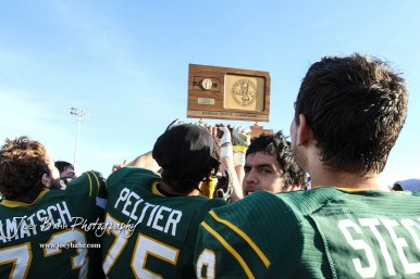 The Pratt Greenbacks hold the State Championship Trophy aloft. The Pratt Greenbacks defeated the Hayden Wildcats 48 to 14 to win the KSHSAA Class 4A Division II State Championship Game at Salina Stadium in Salina, Kansas on November 26, 2016. (Photo: Joey Bahr, www.joeybahr.com)