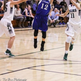 St. John Lady Tiger #12 Bailey Burns passes the ball as two Central Plains Lady Oilers close in. The Central Plains Lady Oilers defeated the St. John Lady Tigers by a score of 87 to 41 at Central Plains High School in Claflin, Kansas on December 13, 2016. (Photo: Joey Bahr, www.joeybahr.com)