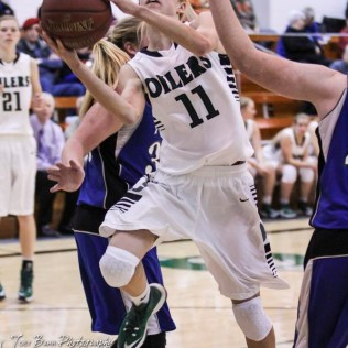 Central Plains Lady Oiler #11 Emily Ryan goes for a layup between two St. John Lady Tigers. The Central Plains Lady Oilers defeated the St. John Lady Tigers by a score of 87 to 41 at Central Plains High School in Claflin, Kansas on December 13, 2016. (Photo: Joey Bahr, www.joeybahr.com)