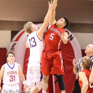 Otis-Bison Cougar #13 Clade Anderson and Hoisington Cardinal #5 Cameron Davis jump for the opening tip off. The Hoisington Cardinals defeated Otis-Bison Cougars 56 to 39 in the Boys Semi-Final of the 2017 Hoisington Winter Jam at Hoisington Activity Center in Hoisington, Kansas on January 20, 2017. (Photo: Joey Bahr, www.joeybahr.com)