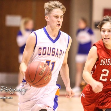 Hoisington Cardinal #25 Braxton Donovan pursues Otis-Bison Cougar #11 Trevor Trapp down the court. The Hoisington Cardinals defeated Otis-Bison Cougars 56 to 39 in the Boys Semi-Final of the 2017 Hoisington Winter Jam at Hoisington Activity Center in Hoisington, Kansas on January 20, 2017. (Photo: Joey Bahr, www.joeybahr.com)