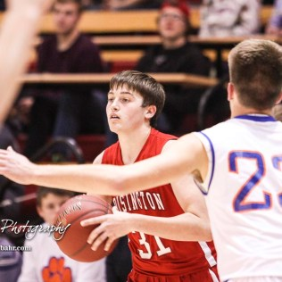 Hoisington Cardinal #31 Kyle Lang looks for a teammate to pass the ball to as Otis-Bison Cougar #23 Maitland Wiltse defends. The Hoisington Cardinals defeated Otis-Bison Cougars 56 to 39 in the Boys Semi-Final of the 2017 Hoisington Winter Jam at Hoisington Activity Center in Hoisington, Kansas on January 20, 2017. (Photo: Joey Bahr, www.joeybahr.com)