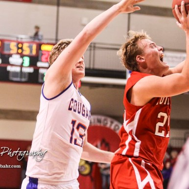 Hoisington Cardinal #22 Grant Dolechek goes past Otis-Bison Cougar #13 Clade Anderson for a layup. The Hoisington Cardinals defeated Otis-Bison Cougars 56 to 39 in the Boys Semi-Final of the 2017 Hoisington Winter Jam at Hoisington Activity Center in Hoisington, Kansas on January 20, 2017. (Photo: Joey Bahr, www.joeybahr.com)