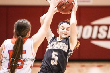 LaCrosse Lady Leopard #5 Abbey Oborny swings the ball as Otis-Bison Lady Cougar #15 Lacey Mitchell defends. The Otis-Bison Lady Cougars defeated the LaCrosse Lady Leopards 61 to 55 in the Girls Semi-Final of the 2017 Hoisington Winter Jam at Hoisington Activity Center in Hoisington, Kansas on January 20, 2017. (Photo: Joey Bahr, www.joeybahr.com)