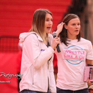 Katherine Shai of the US National Women's Wrestling Team addresses the competitors and spectators at the meet. In the background, Sally Roberts of Wrestle Like a Girl waits for her turn with the mic. The first ever Kansas High School Girls Wrestling Championship was held at the Roundhouse at McPherson High School in McPherson, Kansas on February 11, 2017. (Photo: Joey Bahr, www.joeybahr.com)